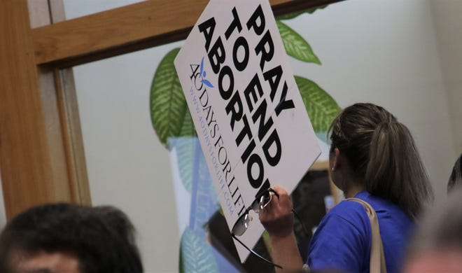 A woman carries a sign opposing abortion, Tuesday, Oct. 8, 2019, as she searches for a seat in the Farmington City Council chambers.