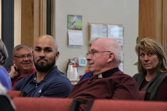 Sacred Heart Catholic Church pastor Father Tim Farrell spoke with others, Tuesday, Oct. 8, 2019, while waiting for the Farmington City Council meeting to start.