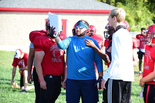 Clarenceville offensive coordinator Derek Smith looks over the next play sheet at practice.