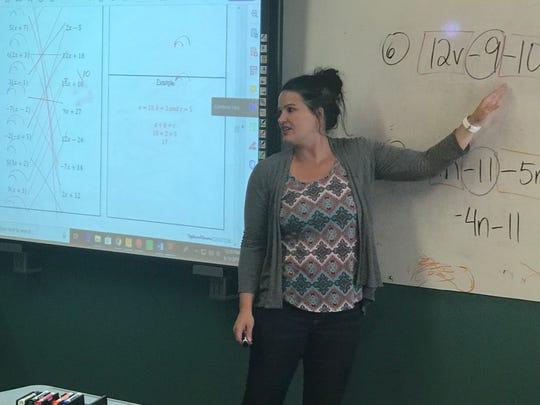 Cambridge High School math teacher Danielle Wensing helps students work out a problem.