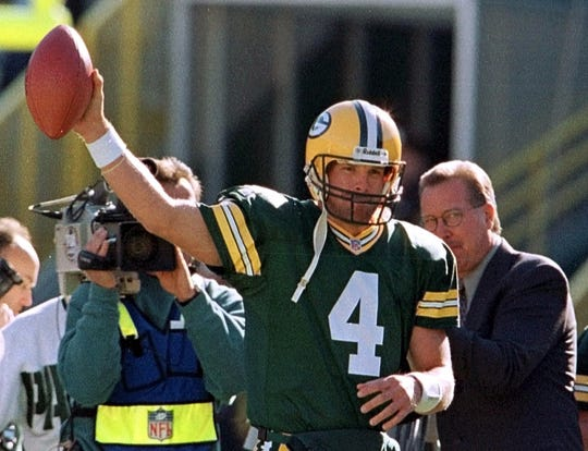 Green Bay Packers quarterback Brett Favre holds up the game ball after taking the first snap in the game against the Chicago Bears Sunday, Nov. 7, 1999, in Green Bay, Wis. The game was Favre's 117th consecutive start, breaking the NFL record held by Ron Jaworski (right). The Bears won 14-13.