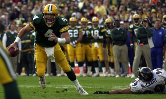 Packers quarterback Brett Favre looks for an open receiver after eluding the grasp of Baltimore Ravens defensive end Michael McCrary during the third quarter of their game on Oct. 14, 2001, at Lambeau Field.