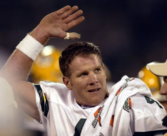 Packers quarterback Brett Favre waves to his wife, Deanna, in a luxury box after throwing his fourth touchdown pass of the game during the second quarter against the Oakland Raiders on Dec. 22, 2003, at Network Associates Coliseum in Oakland, Calif.