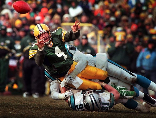 Green Bay Packers quarterback Brett Favre releases a shuttle pass to Dorsey Levens for a first down while in the grasp of Carolina Panthers linebacker Kevin Green during the third quarter of the 1997 NFC Championship game Sunday, January 12, 1997 at Lambeau Field in Green Bay, Wis.