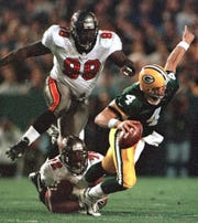 Green Bay Packers quarterback Brett Favre (4) gets away from Tampa Bay Buccaneers Chidi Ahanotu (72) and Warren Sapp (99) to complete a pass in the first quarter on Oct. 10, 1999, in Green Bay.