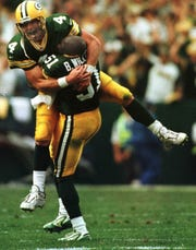 Green Bay Packers quarterback Brett Favre is embraced by teammate Brian Williams after Favre threw a touchdown pass in the waning moments of the fourth during the third quarter of their game against the Minnesota Vikings Sunday, September 26, 1999 at Lambeau Field.