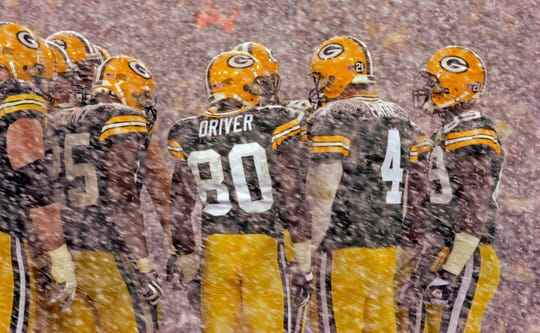 The Green Bay Packers' offensive unit is covered with snow during a break in the fourth quarter of their playoff game against the Seattle Seahawks on Jan. 12, 2008, at Lambeau Field. The Packers defeated the Seahawks 42-20.
