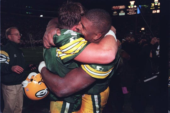 Green Bay Packers defensive end Reggie White (right) gives quarterback Brett Favre a hug after their 23-20 overtime win over the San Francisco 49ers on Oct. 14, 1996, at Lambeau Field in Green Bay.