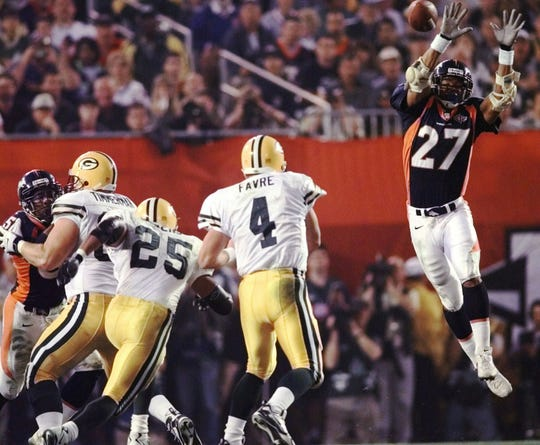 Denver Broncos safety Steve Atwater (27) jumps into the air in an attempt to block Green Bay Packers quarterback Brett Favre's pass during the third quarter of Super Bowl XXXII at San Diego's Qualcomm Stadium on Jan. 25, 1998. At left is Packers' Dorsey Levens (25) and guard Adam Timmerman (63).