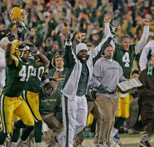 The Green Bay Packer bench and defensive back Chris Johnson (center, street clothes) erupts after Ryan Longwell's game-winning field goal at the end of the game to give the Packers a 34-31 win at Lambeau Field Sunday, November 14, 2004.