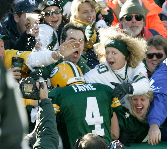 Green Bay Packers quarterback Brett Favre leaps into the crowd after rushing for a touchdown during the third quarter of an NFL football game against the Arizona Cardinals, Sunday, Oct. 29, 2006, in Green Bay.