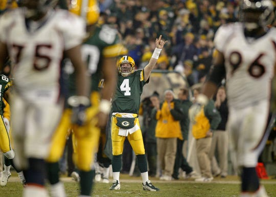 Text: Green Bay Packers Brett Favre reacts after Ahman Green ran 98 yards for a touchdown during the fourth quarter of their game against the Denver Broncos Sunday, December 28, 2003 at Lambeau Field in Green Bay.