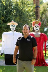 Run With Los Muertos 5K race director, Tizoc DeAztlan, stands next to puppets that will be used in the processional prior to the start of the race in Coachella, Calif., this coming November 2, 2019.