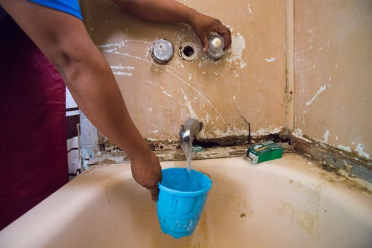 A resident of Oasis Mobile Home Park opens his shower faucet to gather water for cooking. The park was cited by the Environmental Protection Agency for having dangerous levels of arsenic.