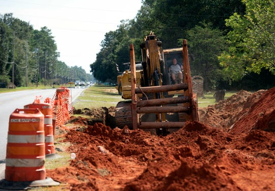 Construction crews install underground utilities off Chumuckla Highway in Milton on Wednesday.