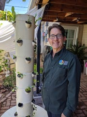 Greg Peterson stands beside his vertical planter, which grows his small greens in his backyard.