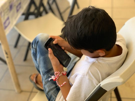 Alex, a 9-year-old from Honduras, plays with his phone on Oct. 2, 2019. He and his mother Welsy Duvo are staying at a migrant shelter in Mexicali after being sent back in September under the Migrant Protection Protocols.