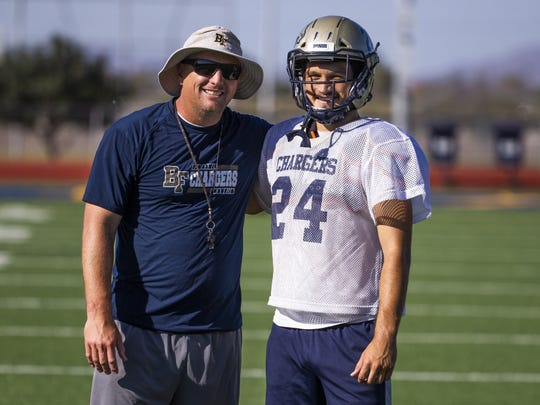 Benjamin Franklin High School football coach Dave Jefferies and his son, Zach Jefferies, a running back, pause at practice, Monday, October 7, 2019.
