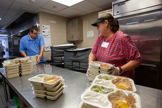 Brandon Mahair and Melissa Williams prepare meals for delivery, Oct. 3, 2019.