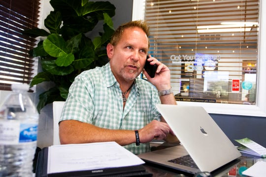 Eric Cheroske, CEO and director of Events at Got You Covered Entertainment, talks to a client in his shared office space.