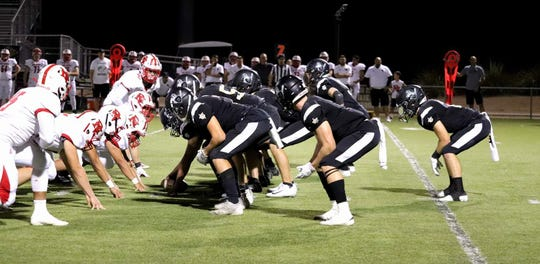 Gilbert Christian football players, right, line up in a Double Wing T offense.