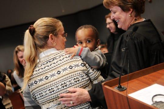 Una mujer sin identificar sujeta a su hijo, a quien adoptó el 17 de noviembre de 2008, en una ceremonia realizada en el condado de Osceola, en Florida, en la que veintiocho menores, varios de ellos hispanos, vieron cumplido su sueño de tener una familia.