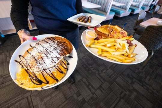 Chocolate chip pancakes, a reuben sandiwch with french fries and a plate of sausages are delivered to a table at Ocean Breeze in Marysville.