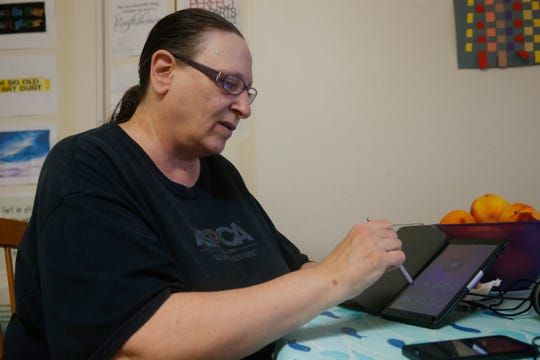 Monica Perez uses her tablet on October 8, 2019.  Perez is part of a pilot program that provides residents in low income housing with internet enabled tablets to help them bridge the technology gap. She uses the tablet to read books & magazines from the library as well as connect with family & friends.