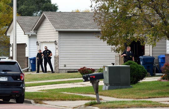Police watch the open garage door of a home after several officers entered the premises in the Northern Heights neighborhood on Wednesday, Oct. 9, in Sioux Falls.