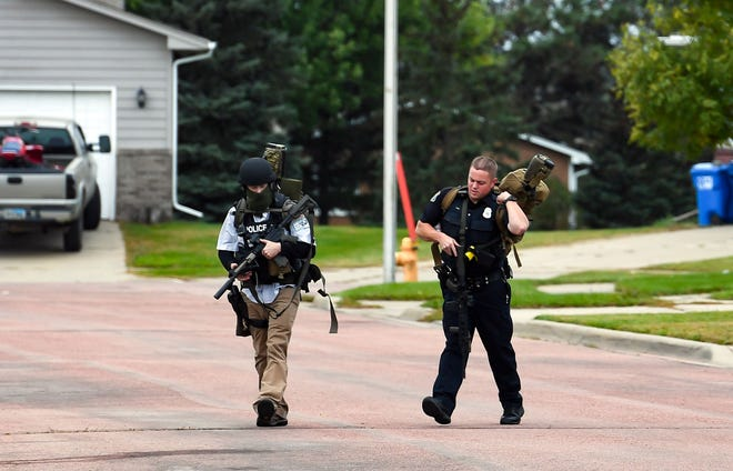 Armed police officers walk down a residential street in the Northern Heights neighborhood on Wednesday, Oct. 9, in Sioux Falls.