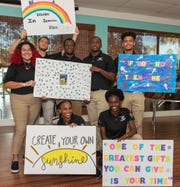 AmeriCorps volunteers with motivational signs they made for the Martin County Boys & Girls Clubs' AmeriCorps Opening Day at Flagler Place in Stuart on Oct. 4, 2019.