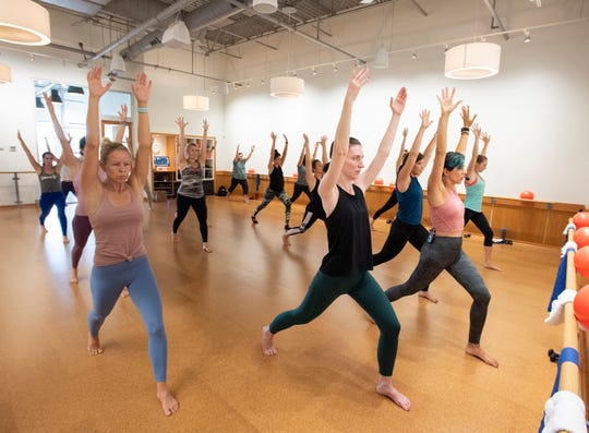 Kyla Sfiris, co-owner of barre3 Five Forks in Simpsonville, leads a warm-up during a recent class.