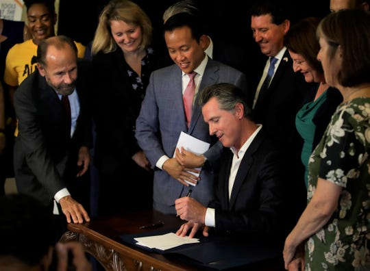 California Gov. Gavin Newsom signs a bill Tuesday in Oakland that will cap rent increases at 5% each year plus inflation. The bill will also ban landlords from evicting tenants without just cause.