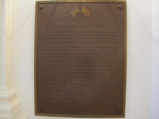 A Maryland panel has voted to remove a Confederate flag from the top of this plaque, as shown in a July 12, 2019 photograph, in the Maryland State House in Annapolis, Md., that honors the Civil War's Union and Confederate soldiers. While the State House Trust voted 3-1 to remove the flags at the top of the sign, it decided to keep the plaque on the wall of the Capitol and overlay an image of the Maryland state flag in their place (AP Photo/Brian Witte)
