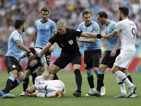 Uruguay players protest to referee Nestor Pitana of Argentina that France's Kylian Mbappe, on the ground, is overreacting after taking a dive during the quarterfinal match between Uruguay and France at the 2018 soccer World Cup in the Nizhny Novgorod Stadium, in Nizhny Novgorod, Russia, Friday, July 6, 2018.