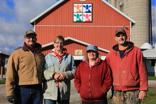 "The barn quilt ""Cows of a Different Color,"" was a gift to David and Dyan Gwidt, right, from David's sister, Mary Ann Mynsberge, pictured second from left with her husband, Larry."