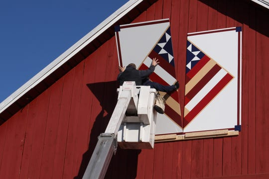 An employee of Raddant Electric of Shawano places the second 4x8-foot section of a barn quilt in place.