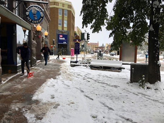 People clear the sidewalk after a fall snowstorm in Helena, Mont., on Wednesday, Oct. 9, 2019.