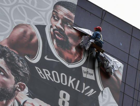A worker removes a promotional banner from a building for the NBA preseason games in China between the Brooklyn Nets and the Los Angeles Lakers.
