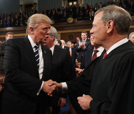 President Donald Trump shakes hands with Chief Justice John Roberts at the State of the Union address in 2017. If the Senate holds an impeachment trial, Roberts would be the presiding officer.
