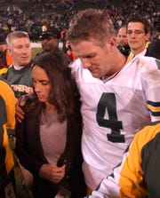 "Green Bay Packers quarterback Brett Favre is escorted off the field with his wife, Deanna, after the Packers defeated the Oakland Raiders, 41-7, ""Monday Night Football"" on Dec. 22, 2003 in Oakland.  Favre's father passed away the day before."
