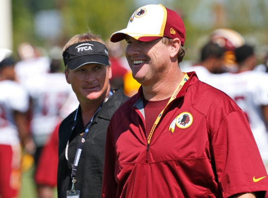Jon Gruden before his second stint as Oakland Raiders coach visits his brother Jay at Washington Redskins practice in 2014. Jay was fired Monday.