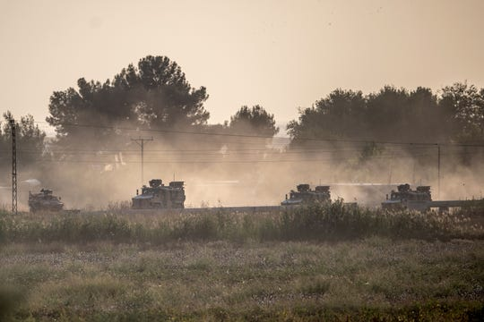 Turkish army vehicles drive toward the Syrian border on Oct. 9, 2019.