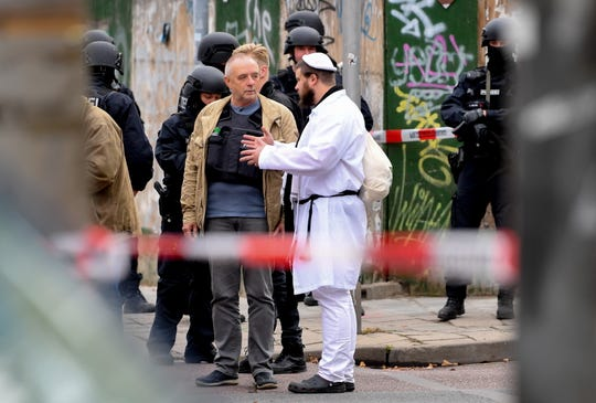 A synagogue visitor talks to police after shooting at a synagogue in Halle, Germany, October 9, 2019. According to the policeman two were shot in front of Synagogue and Kebab's shop in the Paulus area of Halle in the eastern German state in Saxony. Anhalt. The police said a suspect is being arrested. The media reports that Halle's mayor talks about the state of amok.