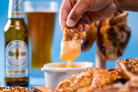 Dipping Bavarian pretzels in beer cheese sauce.