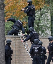 Police officers cross a wall at a crime scene in Halle, Germany, on Oct. 9, 2019. A gunman fired several shots on Wednesday in the German city of Halle. Police say a person has been arrested after a shooting that left two people dead.