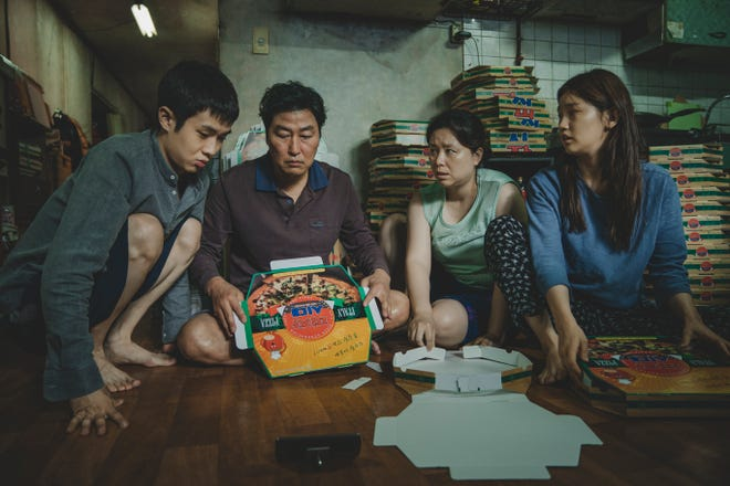 "The poor Kim family (Choi Woo-shik, from left, Song Kang-ho, Jang Hye-jin and Park So-dam) go from folding pizza boxes to running a mini-mansion in the South Korean dramedy ""Parasite."""