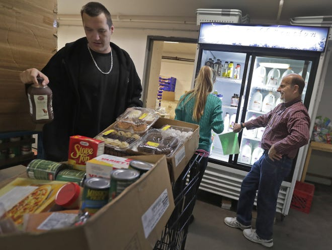 Volunteer Paul Schneider, right, helps James and Danielle Best of Neenah select groceries at the Salvation Army food pantry in Appleton.