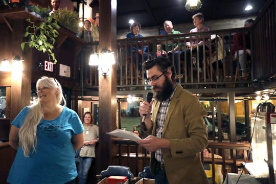 Cindy Siegel, left, of Kaukauna participates in a trivia contest with Richie Zaborowske, a Neenah librarian, Wednesday at McFleshman's Brewing Co., in Appleton. The Short Story Night was part of the Fox Cities Book Festival.