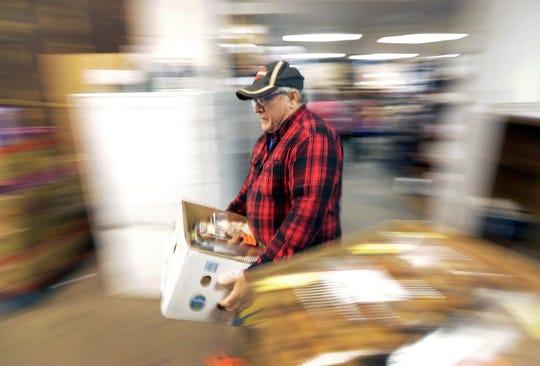 Volunteer  Paul Van Straten carries groceries at the Salvation Army food pantry in Appleton.